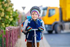 Little kid boy in helmet riding with his scooter in the city royalty free stock image