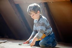 Little kid boy helping with toy tools on construciton site. Little kid boy helping with toy tools on construction site. Funny child of 6 years having fun on Stock Image