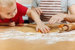 Little kid boy helps mother to cook ginger biscuit. Happy family mom and child in weekend morning at home. Relationship. The little kid boy helps mother to cook royalty free stock photos
