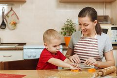 Little kid boy helps mother to cook ginger biscuit. Happy family mom and child in weekend morning at home. Relationship. The little kid boy helps mother to cook stock photo