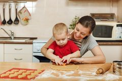 Little kid boy helps mother to cook ginger biscuit. Happy family mom and child in weekend morning at home. Relationship. The little kid boy helps mother to cook stock images