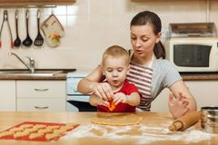 Little kid boy helps mother to cook ginger biscuit. Happy family mom and child in weekend morning at home. Relationship. The little kid boy helps mother to cook royalty free stock photography