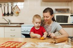 Little kid boy helps mother to cook ginger biscuit. Happy family mom and child in weekend morning at home. Relationship. The little kid boy helps mother to cook stock photography