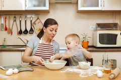 Little kid boy helps mother to cook ginger biscuit. Happy family mom and child in weekend morning at home. Relationship. Little kid boy helps mother to cook stock images