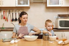 Little kid boy helps mother to cook ginger biscuit. Happy family mom and child in weekend morning at home. Relationship. Little kid boy helps mother to cook stock photography