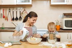 Little kid boy helps mother to cook ginger biscuit. Happy family mom and child in weekend morning at home. Relationship. Little kid boy helps mother to cook royalty free stock photography