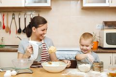 Little kid boy helps mother to cook ginger biscuit. Happy family mom and child in weekend morning at home. Relationship. Little kid boy helps mother to cook stock image