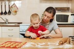 Little kid boy helps mother to cook ginger biscuit. Happy family mom and child in weekend morning at home. Relationship. The little kid boy helps mother to cook royalty free stock photo