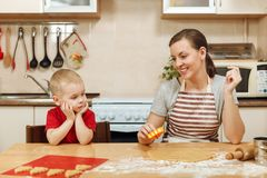 Little kid boy helps mother to cook ginger biscuit. Happy family mom and child in weekend morning at home. Relationship. The little kid boy helps mother to cook stock image