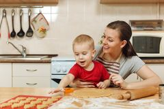 Little kid boy helps mother to cook ginger biscuit. Happy family mom and child in weekend morning at home. Relationship. The little kid boy helps mother to cook royalty free stock images