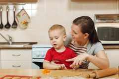 Little kid boy helps mother to cook ginger biscuit. Happy family mom and child in weekend morning at home. Relationship. The little kid boy helps mother to cook royalty free stock image