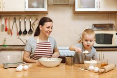 Little kid boy helps mother to cook ginger biscuit. Happy family mom and child in weekend morning at home. Relationship. Little kid boy helps mother to cook royalty free stock photo