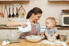 Little kid boy helps mother to cook ginger biscuit. Happy family mom and child in weekend morning at home. Relationship. stock image