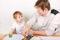 Little kid boy and his dad having fun with making handpaints Stock Images