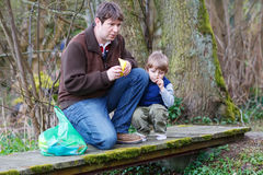 Little kid boy and his dad playing together with colorful paper. Boats by a river on spring or autumn day. Creative leisure with kids Royalty Free Stock Photo