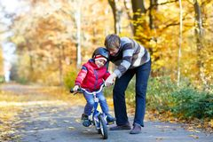 Little kid boy and his father in autumn park with a bicycle. Dad teaching his son biking Stock Photography