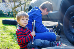 Little kid boy and his father changing wheel on car Royalty Free Stock Photos