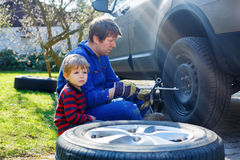 Little kid boy and his father changing wheel on car Royalty Free Stock Images