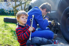 Little kid boy and his father changing wheel on car Royalty Free Stock Image