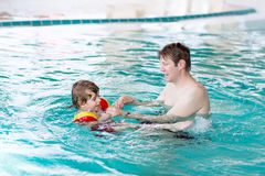 Little kid boy and his father swimming in an indoor pool Royalty Free Stock Photography