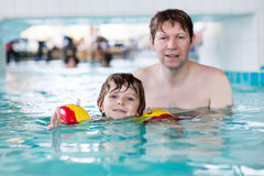 Little kid boy and his father swimming in an indoor pool Royalty Free Stock Images