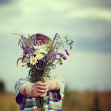 Little kid boy holding bouquet of fields flowers. Child giving flowers. Stock Image