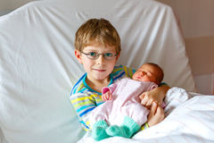 Little kid boy holding his sleeping newborn baby sister in hospital. Happy laughing kid boy with glasses holding his sleeping newborn baby sister in hospital Royalty Free Stock Images