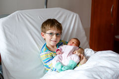 Little kid boy holding his sleeping newborn baby sister in hospital. Happy laughing kid boy with glasses holding his sleeping newborn baby sister in hospital Stock Photo