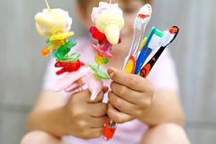 Little kid boy holding marshmallow skewer in one hand and toothbrushes in another Stock Photos
