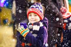 Little kid boy with hot chocolate on Christmas market Royalty Free Stock Photos
