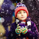 Little kid boy with hot chocolate on Christmas market Royalty Free Stock Image