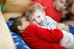 Little kid boy hugging with newborn baby girl, cute sister. Brother on background Stock Image