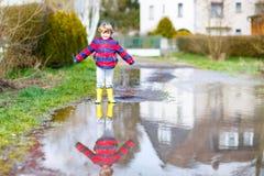 Free Little Kid Boy Jumping Through Rain Puddle Stock Photos - 79241013
