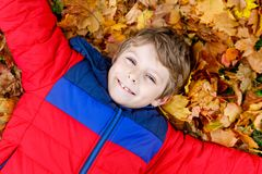 Little kid boy lying in autumn leaves in colorful fashion fall clothing. Royalty Free Stock Photography