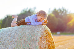 Little kid boy lying on hay stack  and smiling Royalty Free Stock Image