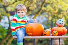 Little kid boy making jack-o-lantern for halloween in autumn gar. Den, outdoors. Having fun on sunny warm october day Stock Photography