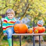 Little kid boy making jack-o-lantern for halloween in autumn gar. Den, outdoors. Having fun on sunny warm october day Royalty Free Stock Photo