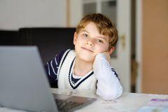 Little kid boy making school homework on computer notebook. Happy healthy child searching information on internet. New. Media education, kid watching learning royalty free stock photography