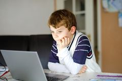 Little kid boy making school homework on computer notebook. Happy healthy child searching information on internet. New. Media education, kid watching learning royalty free stock image