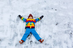 Little kid boy making snow angel in winter Royalty Free Stock Photography
