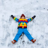 Little kid boy making snow angel in winter, outdoors Royalty Free Stock Photography