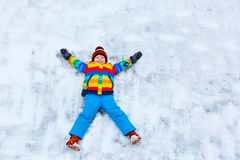 Little kid boy making snow angel in winter, outdoors Royalty Free Stock Image