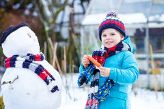 Little kid boy making a snowman in winter Royalty Free Stock Photography
