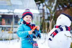 Little kid boy making a snowman in winter Royalty Free Stock Photos
