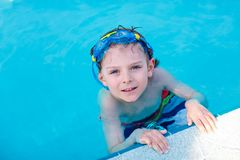 Little kid boy making swimming competition in pool. Happy little preschool kid boy making swimming competition. Child having fun in an swimming pool. Active Stock Images