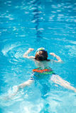 Little kid boy making swimming competition in pool. Happy little preschool kid boy making swimming competition. Child having fun in an swimming pool. Active Royalty Free Stock Photos