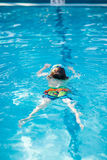 Little kid boy making swimming competition in pool. Happy little preschool kid boy making swimming competition. Child having fun in an swimming pool. Active Royalty Free Stock Image