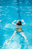 Little kid boy making swimming competition in pool. Happy little preschool kid boy making swimming competition. Child having fun in an swimming pool. Active Royalty Free Stock Images