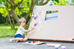 Little kid boy painting big paper house with colorful paintbox Stock Images