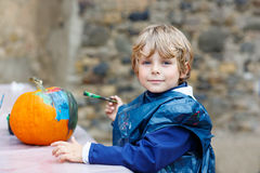 Little kid boy painting with colors on pumpkin Stock Photos